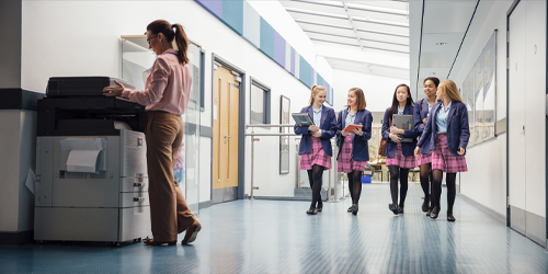 A group of school girls walking together in a school hallway smiling while a woman is using a printer in the foreground.